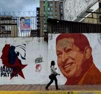 CARACAS, Venezuela.- Una mujer camina cerca de un mural que conmemora a Hugo Chávez. Foto: AFP.