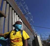Migrantes se concentran en el cruce Chaparral la frontera México-EEUU en Tijuana. Foto: AP.