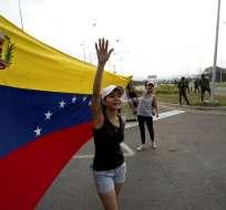 UREÑA, Venezuela.- Una mujer grita que la ayuda humanitaria es bienvenida mientras ondea una bandera venezolana. Foto: AP.