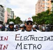 CARACAS, Venezuela.- Seguidores de Guaidó desafían a un contingente de antimotines en marcha. Foto: AFP.