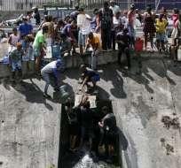 CARACAS, Venezuela.- Personas colectan agua de una cañería rota en uno de los canales de agua servida del río Guaire. Foto: AFP.