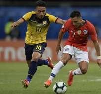 Ángel Mena de Ecuador lucha el balón ante Alexis Sánchez.