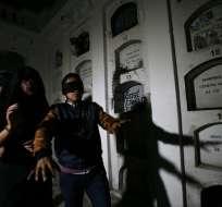 Turistas con los ojos vendados caminan por el cementerio de El Tejar, en el centro de Quito, el 11 de septiembre. Foto: AP