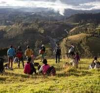 Migrantes venezolanos miran hacia la Carretera Panamericana desde una loma con césped, en Urbina. Foto: AP