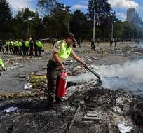 QUITO, Ecuador.- Policías también han participado en la limpieza y extinción de los focos de fuego en las calles. Foto: AFP