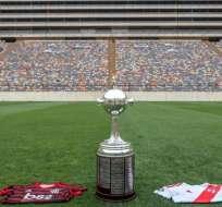 Trofeo de la Copa Libertadores con las camisetas de los equipos de la final.