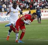 Martínez Borja de Liga disputa el balón con el portero de Universidad Católica.