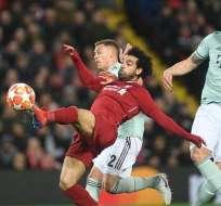 Salah (rojo) se estira para alcanzar un balón con el pie.
