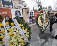 os hombres colocan dos coronas de flores junto a una fotografía del expresidente Nelson Mandela en la embajada sudafricana en Pekín, China. Foto: EFE