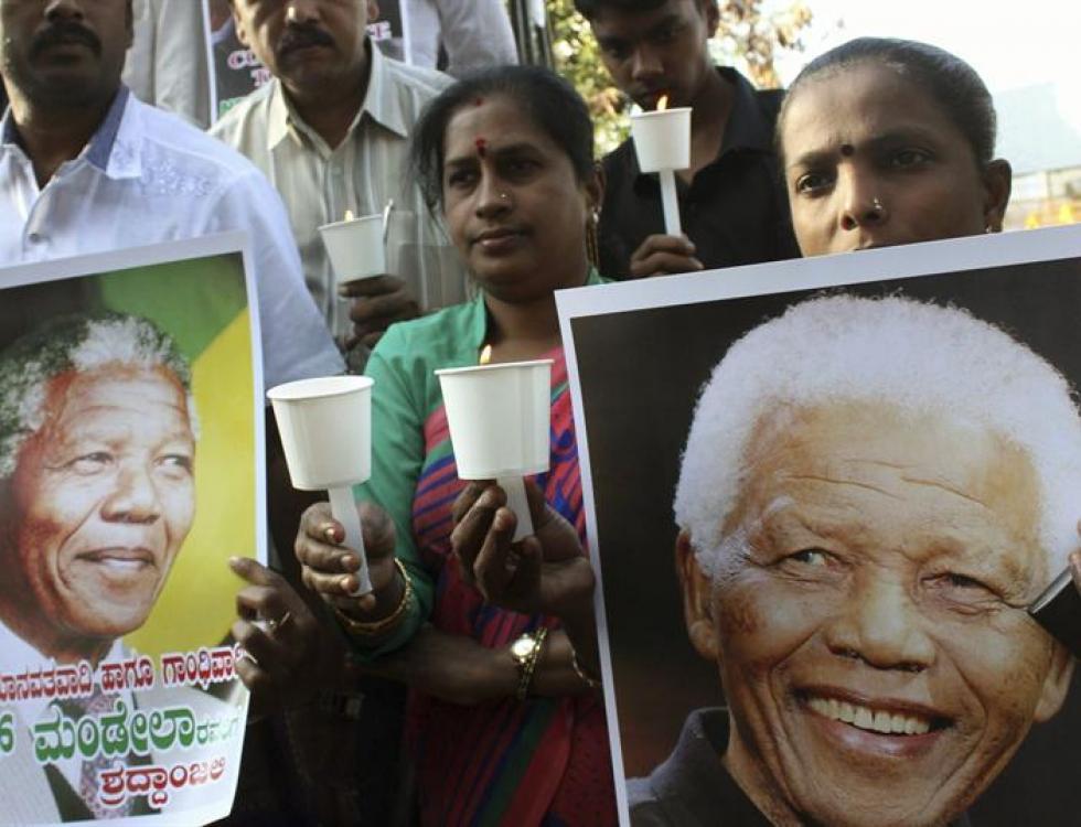 Mujeres y hombres encienden velas mientras honran al expresidente sudafricano Nelson Mandela en Bangalore, India. Foto: EFE