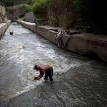 Douglas saca un puñado de lodo del fondo del contaminado río Guaire para buscar oro y cualquier cosa valiosa que pueda vender.