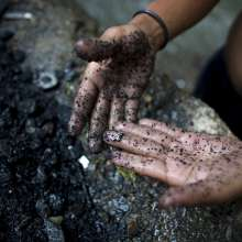 Un chatarrero muestra una cruz de plata que encontró en el fondo del contaminado río Guaire.