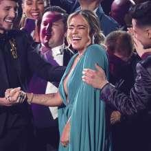 Miembros de la audiencia felicitan a Karol G antes de que ésta suba al escenario a recibir el Latin Grammy. Foto: AP.