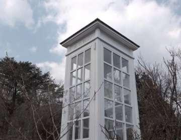 La cabina blanca contiene un teléfono negro antiguo desconectado.