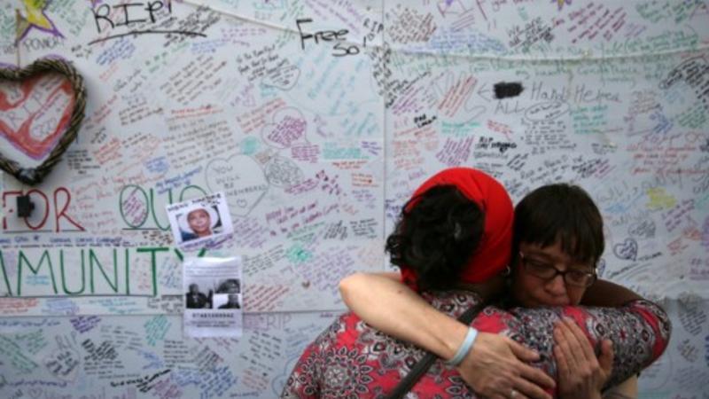 Dos mujeres se abrazan frente a los mensajes dejados en una pared de condolencia tras el incendio en la Torre Grenfell, bloque residencial consumida por un incendio
