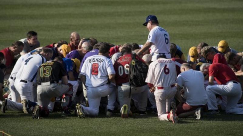 Los miembros del equipo republicano dedican una oración antes de un juego de béisbol del Congreso entre demócratas y republicanos en el Nationals Estadio en Washington, DC