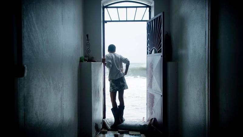 Una residente de Saint-Pierre, en la isla de las Antillas francesas de Martinica, contempla el fuerte oleaje desde el umbral de su puerta. Martinica, barrida por el huracán María el martes pasado, ha sufrido cortes en el servicio eléctrico, aunque por suerte no se han producido daños importantes.