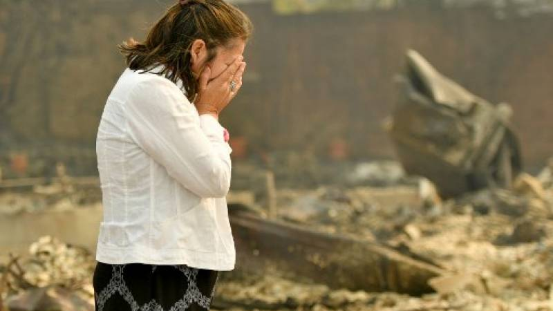 Los propietarios de viviendas Martha Márquez miran por encima de su hogar quemado en Santa Rosa, California
