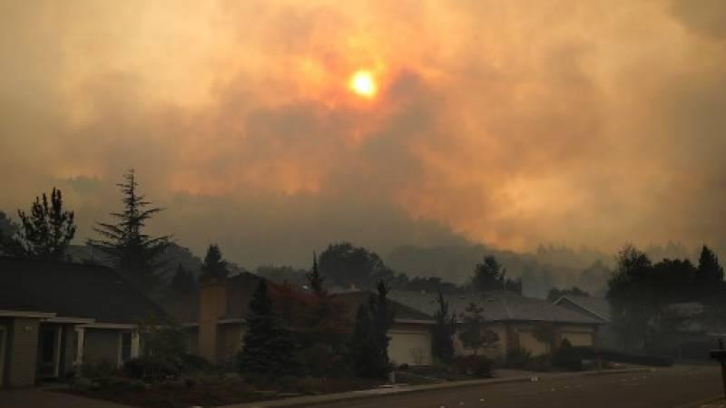 El humo se agita de las colinas sobre hogares en la vecindad de Oakmont en Santa Rosa, California.