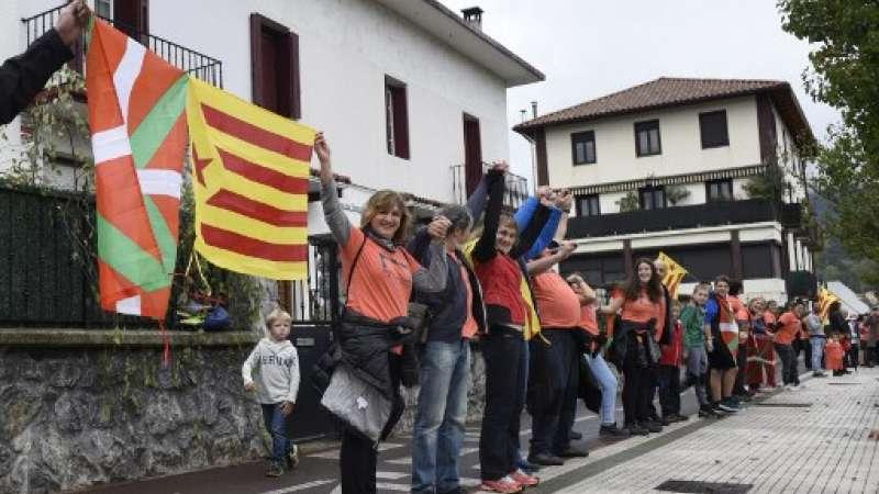 La gente sostiene banderas catalanas pro-independentistas de Estelada y banderas del País Vasco cuando participan en una cadena humana entre aldeas en el pueblo vasco de Lazkao