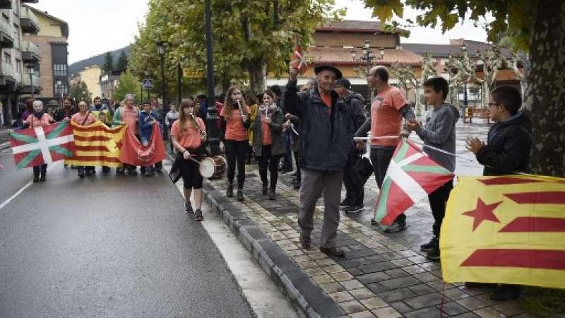 Personas portando banderas de Estelada catalanas independentistas y banderas del País Vasco durante una manifestación en el pueblo vasco de Beasain, al norte de España