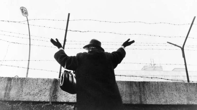 Una señora saluda desde el sector Oeste a sus conocidos del sector Este, 1961.