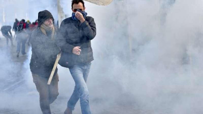 Las personas se protegen de las granadas de humo durante un día de protesta nacional contra las reformas económicas y sociales del gobierno