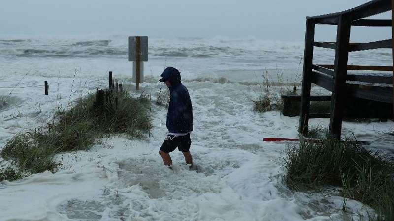 Cameron Sadowski camina por donde las olas se estrellan en la playa Foto: AFP